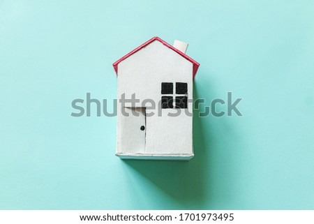 Simply design with miniature white toy house isolated on blue pastel colorful trendy background. Mortgage property insurance dream home concept. Flat lay top view copy space