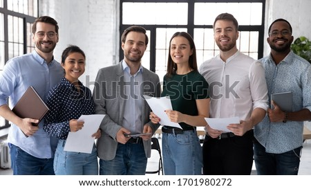 Group portrait of smiling diverse young multiethnic businesspeople posing together in modern office, happy motivated multiracial employees show unity and success, teamwork, cooperation concept #1701980272