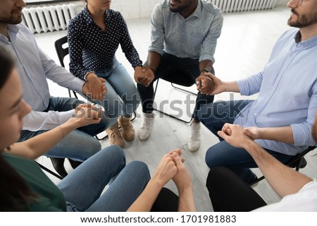 Close up top view of diverse young people sit in circle holding hands participate in group therapy, multiracial patients give psychological help or support engaged in counseling session together #1701981883