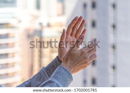 Woman hands applauding medical staff from balcony. People in Spain clapping gratitude on balconies and windows in support of health workers, doctors and nurses during the Coronavirus pandemic #1702001785