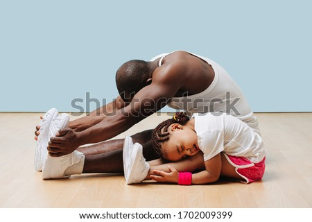 Father and his little daughter stretching knees and backs on the floor at home, folding themselves. Pained faces, feeling tension in ligaments and sinews. #1702009399
