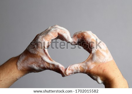 Male soaped hands on a light gray bathroom background. Hygiene concept. Palms metaphorically depict the heart #1702015582