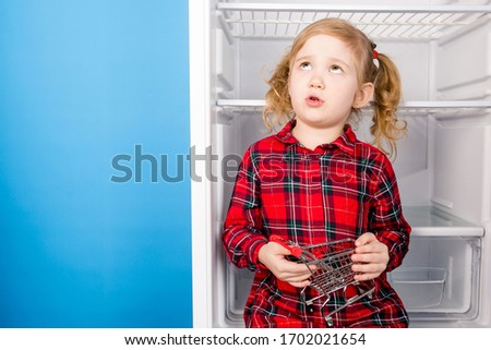 Thoughtful cute child sitting in an empty refrigerator holding a small grocery cart. Waiting for food delivery. Quarantine shortage of food in the house #1702021654