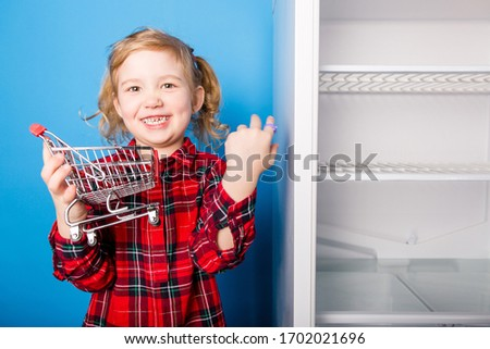 Happy child with a grocery cart in hands standing on a blue background next to an empty refrigerator #1702021696
