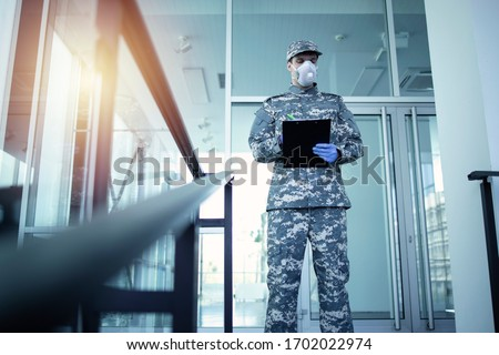 Soldier in military camouflage uniform with rubber gloves and mask guarding in front of hospital's door and controlling who gets in and out. Military helping in fight against coronavirus or COVID-19. #1702022974