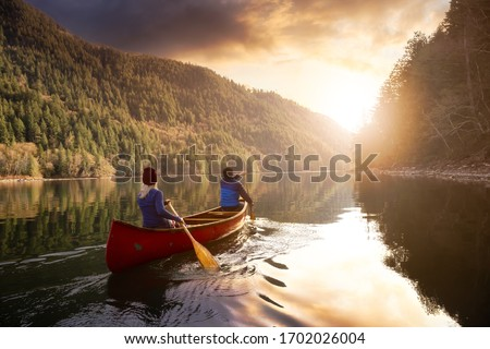 Couple friends canoeing on a wooden canoe during a colorful sunny sunset. Cloudy Sky Composite. Taken in Harrison River, East of Vancouver, British Columbia, Canada. Royalty-Free Stock Photo #1702026004
