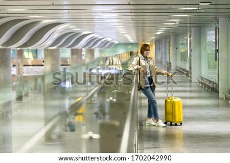 Woman with luggage stuck at empty airport terminal due to coronavirus pandemic/Covid-19 outbreak travel restrictions. Flight cancellation. Travel industry financial crisis.Quarantine isolation measure #1702042990