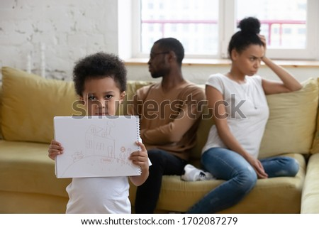 Close up african american boy suffering from parents conflict at home in living room and holding picture. Sad son frustrating hear mother and father fighting arguing, family conflict, divorce.