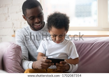 Smiling African American father with little son playing game on smartphone using online networks at home, happy black dad embracing little child, sitting on cozy sofa.