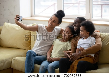 African American parent with two kids taking selfie, smiling woman holding phone, happy husband with son and daughter posing for photo with wife, family having fun together with gadget. #1702087366