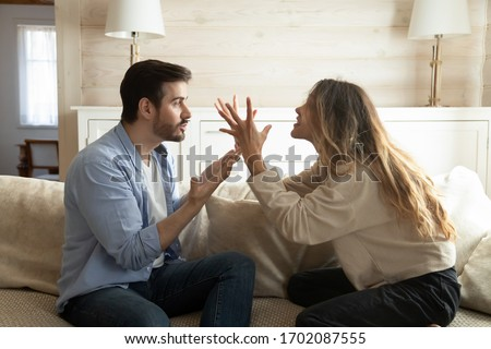Emotional annoyed stressed couple sitting on couch, arguing at home. Angry irritated nervous woman man shouting at each other, figuring out relations, feeling outraged, relationship problems concept. Royalty-Free Stock Photo #1702087555