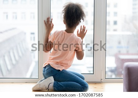 Waiting african adolescent girl sitting alone on windowsill in living room at home. Young single female person thinking staring at window. Sad daughter feel upset. Youth problems, adoption concept Royalty-Free Stock Photo #1702087585