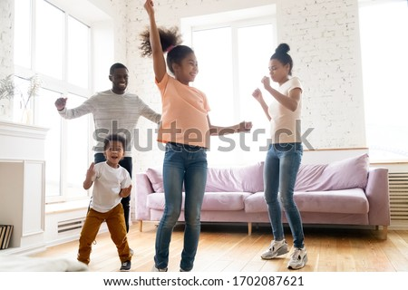 Happy loving young african american family dancing to favorite song at home. Smiling dad and mom teaching young girl and boy modern style. Having fun together with two cute little kids in living room #1702087621
