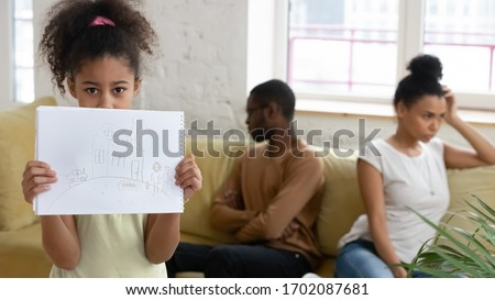 Close up african american girl suffering from parents conflict at home in living room and holding picture. Sad daughter frustrating hear mother and father fighting arguing, family conflict, divorce.