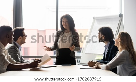 Middle-aged businesswoman stand lead team meeting with diverse multiracial colleagues in office, motivated Asian female CEO or boss talk at briefing with diverse coworkers, leadership concept #1702087915