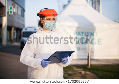 Paramedic wearing personal protective equipment PPE holding folder standing in front of ICU hospital isolation rt-PCR drive thru testing site,COVID-19 pandemic outbreak crisis,worried exhausted staff #1702088257