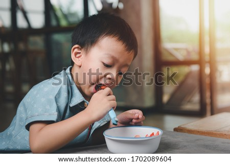 Portrait asian Boy 3 years old Smiling happily While eating snacks. The joy of eating for children concept. #1702089604