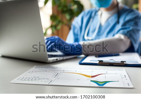 Epidemiologist doctor working on laptop computer,analyzing graphs & charts,COVID-19 Coronavirus global pandemic crisis outbreak,mortality rate death toll statistics,research & data comparison,WHO info #1702100308