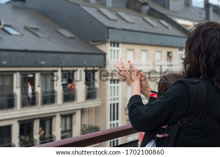 a mother and her baby applauding from the balcony in solidarity with the health personnel who are healing the covid-19 #1702100860