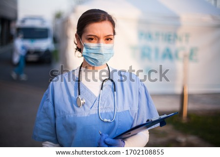 Portrait of very tired  exhausted UK NHS ICU doctor in front of hospital,emergency patient triage tent in background,Coronavirus COVID-19 pandemic outbreak crisis,medical staff working long shifts   Royalty-Free Stock Photo #1702108855
