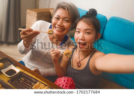 Asian cheerful female friends having Japanese sushi for lunch - happy and attractive woman taking selfie picture on hand phone with her girlfriend eating sushi rolls at home enjoying together