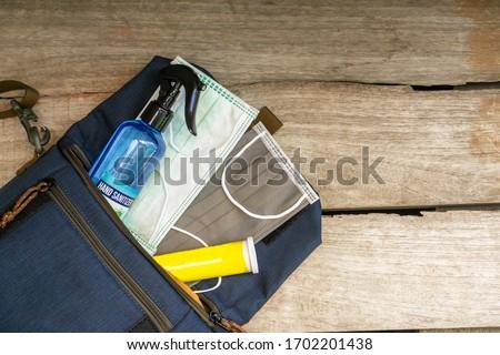 """Defense against Covid-19"" starter pack. Surgical masks, hand sanitizer, vitamin falling out of bag. Corona virus prevention pack. Ear loop Medical mask. New normal starter pack. Royalty-Free Stock Photo #1702201438"