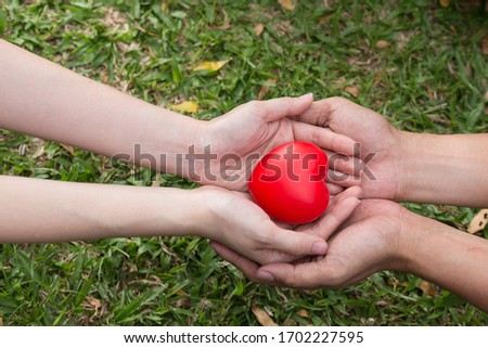 Hand hold red cartoon balloon heart and show to tell save heart and health.green grass background