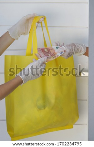Volunteer woman brings a bag with food and other unnecessary groceries for persons in need. Delivery to the door. Food delivery services during coronavirus pandemic. #1702234795