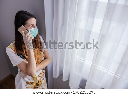 Young woman with face mask and gloves talking on mobile phone. Feeling lonely during isolation. Quarantine melancholy. Stay at home. #1702235293