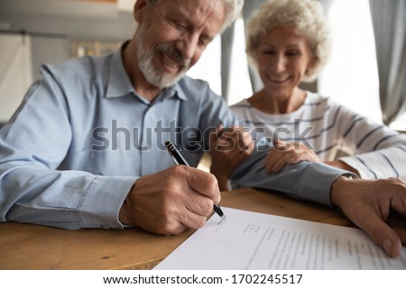 Close up satisfied older couple signing documents, making purchasing or investment deal, smiling mature husband and wife holding hands, putting signature on contract, buying house or taking loan
