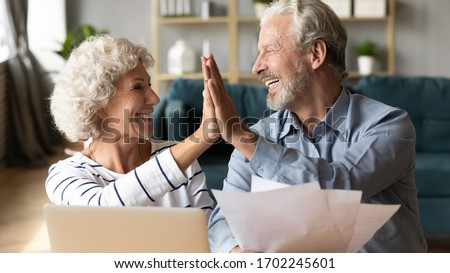Excited older couple giving high five, mature family celebrating success, checking or paying domestic bills, planning budget, smiling mature man holding financial documents, reading good news #1702245601