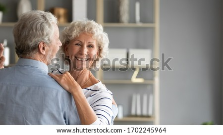 Head shot portrait smiling older woman dancing with man, happy mature wife and husband hugging, standing in living room, senior family enjoying tender moment, celebrating anniversary #1702245964