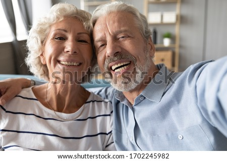 Head shot portrait happy senior couple taking selfie, having fun with phone cam, smiling aged wife and husband hugging, looking at camera, posing for photo, aged man vlogger recording video