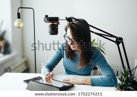 Online content creator vlogger. A young women blogger with glasses removes the content for the blog, training courses. The concept of online learning to draw on the tablet. #1702274251