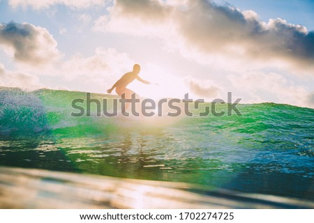 March 15, 2020. Bali, Indonesia. Surfer man on surfboard during surfing. Surfer ride on ocean wave. #1702274725