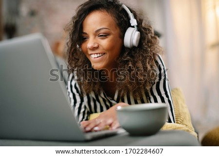 African businesswoman in office. Beautiful woman listening music in office.  #1702284607