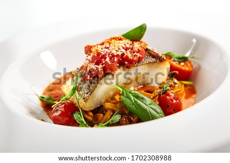 Halibut steak in crispy breading close up. Served cuisine. Dish with fish fillet and zucchini spaghetti in tomato sauce in white plate isolated. Restaurant food portion, delicious supper, main course
