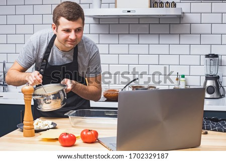 Young man wearing black apron in the modern kitchen looking for recipes on his laptop. Cooking in home, online recipe, remote cooking classes #1702329187