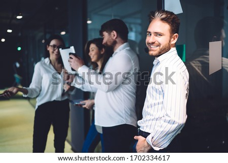 Side view of handsome executive male in formal wear standing with colleagues watching tablet on background in modern office smiling at camera  #1702334617