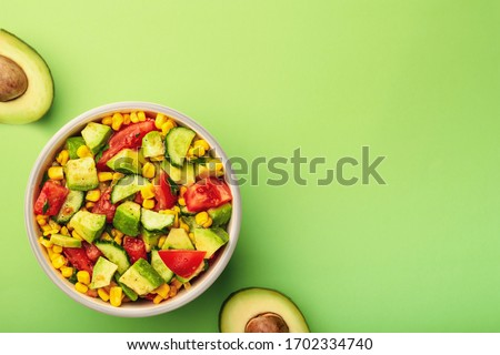 Tasty avocado salad with tomatoes, cucumbers in bowl on green background with copy space. #1702334740