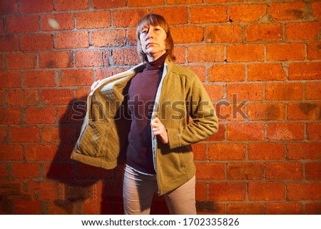 A middle-aged woman poses showing clothes near red brick wall. An inept model in non-professional shooting. Photography for sales short cardigan on the Internet or online store