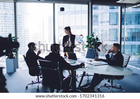 Female corporate director in formal clothing training group of successful professionals during brainstorming conference for search strategy solutions, financial experts discussing business contract #1702341316