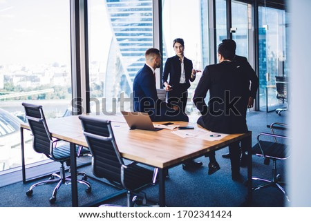 Diverse corporate professionals discussing business ideas during briefing meeting in office workspace, formally dressed executive managers have CEO conversation for talking and consultancy indoors #1702341424