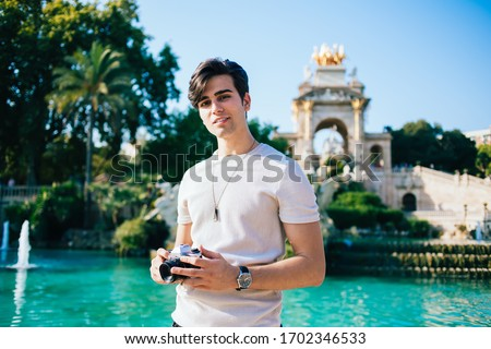 Portrait of handsome positive caucasian male looking at camera standing on urban setting historical center on summer sunny day, photographer enjoying exploring destination on weekends After quarantine #1702346533