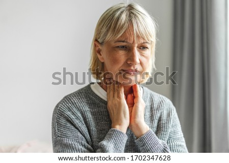 Sick senior adult elderly women touching the neck feeling unwell coughing with sore throat pain.Healthcare and medicine concept Royalty-Free Stock Photo #1702347628