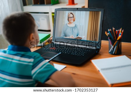 Distance learning online education. A schoolboy boy studies at home and does school homework. A home distance learning. #1702353127