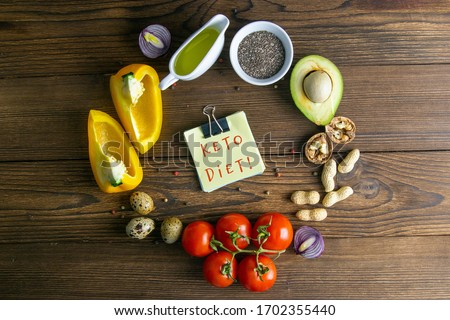 Keto diet. Vegetables and nuts are lined in the shape of a circle, inside a sticker with text KETO DIET. Top views clear space. Royalty-Free Stock Photo #1702355440