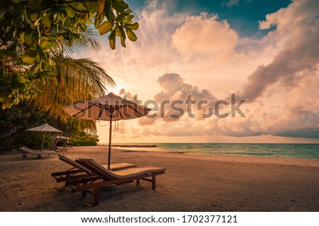 Beautiful beach. Chairs on the sandy beach near the sea. Summer holiday and vacation concept for tourism. Inspirational tropical landscape. Tranquil scenery, relaxing beach, tropical landscape design Royalty-Free Stock Photo #1702377121