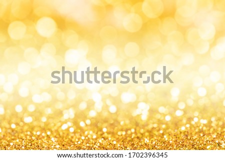 Gold glitter texture. Sparkling gold bright bokeh from blurred diamond dust on black background. Abstract golden bokeh background. Selective focused