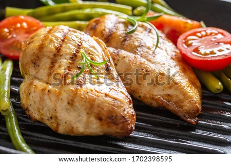 Barbecued chicken breasts on a grill pan with fresh green vegetable and chery tomatoes and rosemary twigs. #1702398595